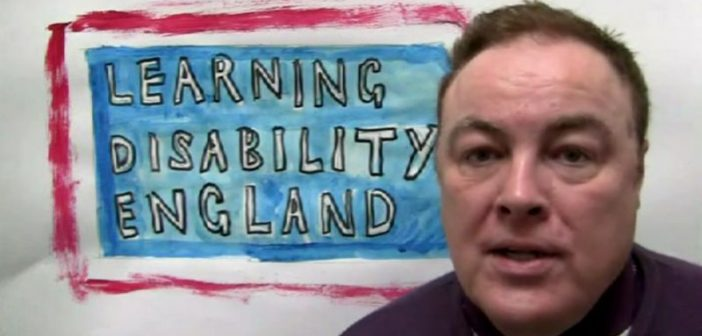 Gary Bourlet in front of a sign saying Learning Disability England