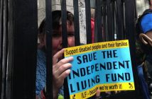 A woman peers out from between fake bars holding a 'Save the Independent Living Fund' sign