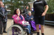 Sandra Daniels sitting in wheelchair speaking into a loudspeaker