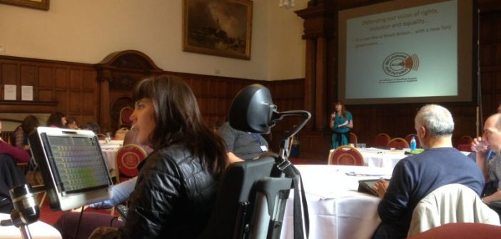 A female wheelchair-user listens as a woman with a microphone speaks in the background