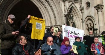 Disabled people in front of the Royal Courts of Justice, with a banner for Inclusion London
