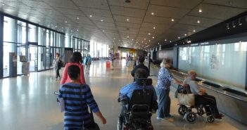 A wheelchair-user and two other people walk away from the camera down a long, wide modern space