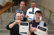 Four people standing on steps, each holding pieces of paper with Scotland 2021 written on them