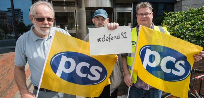Three people, two holding PCS flags and one holding a small #Defend82 poster