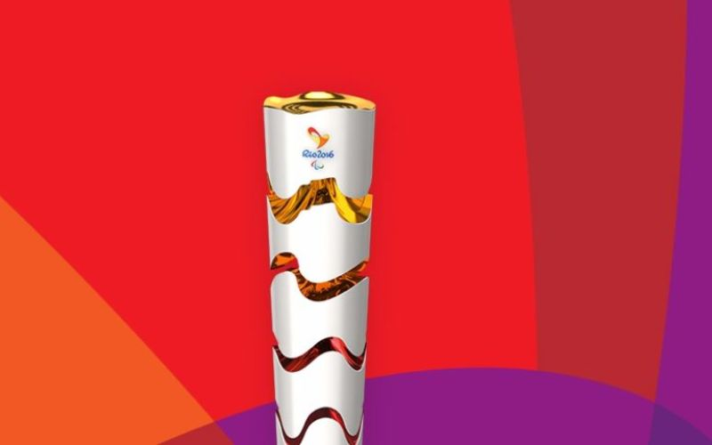 The Rio 2016 torch against a colourful background