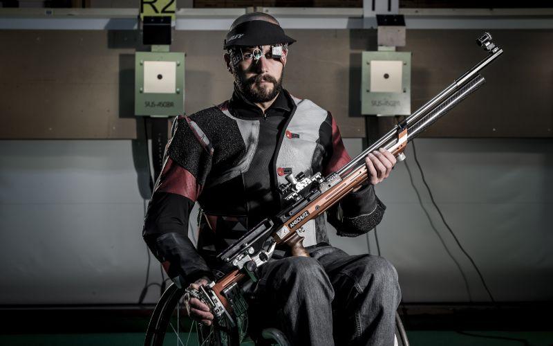 Matt Skelhon in his wheelchair, holding a gun