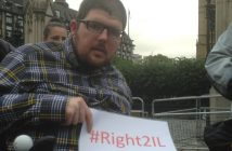 A protester holds a sign saying #Right2IL