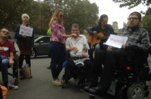 One protester sings, while another plays a guitar and others hold up placards