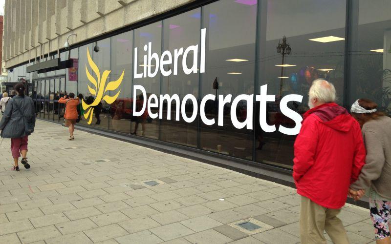Man walks past Liberal Democrat logo on a long window
