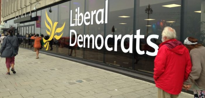 Man walks past Liberal Democrat logo on a long window