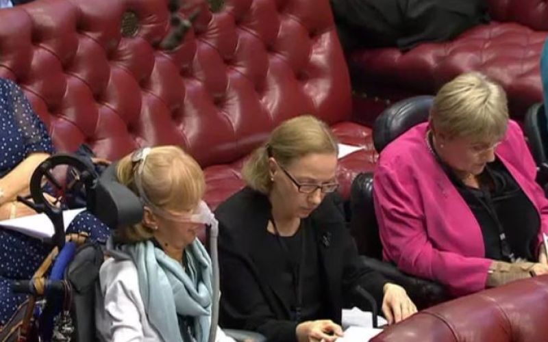 Baroness Campbell speaking in the debate, next to her PA and then Baroness Brinton