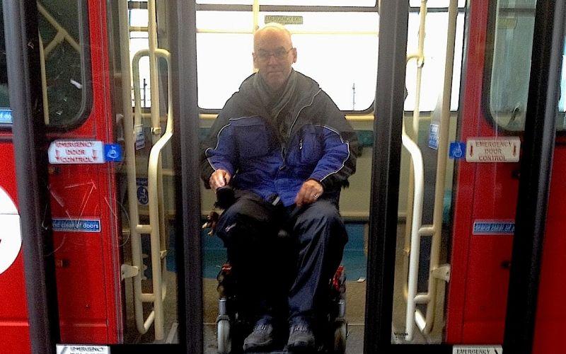 Chris Stapleton in his wheelchair in the doorway of a bus
