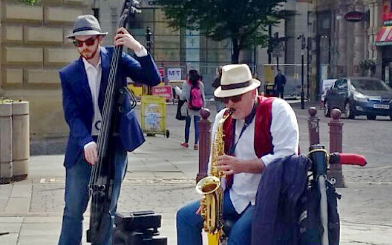 Guy Stewart playing saxophone from his scooter accompanied by his son on electronic double bass