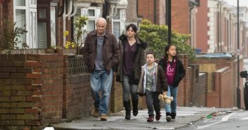 Four characters from the film walk down a street
