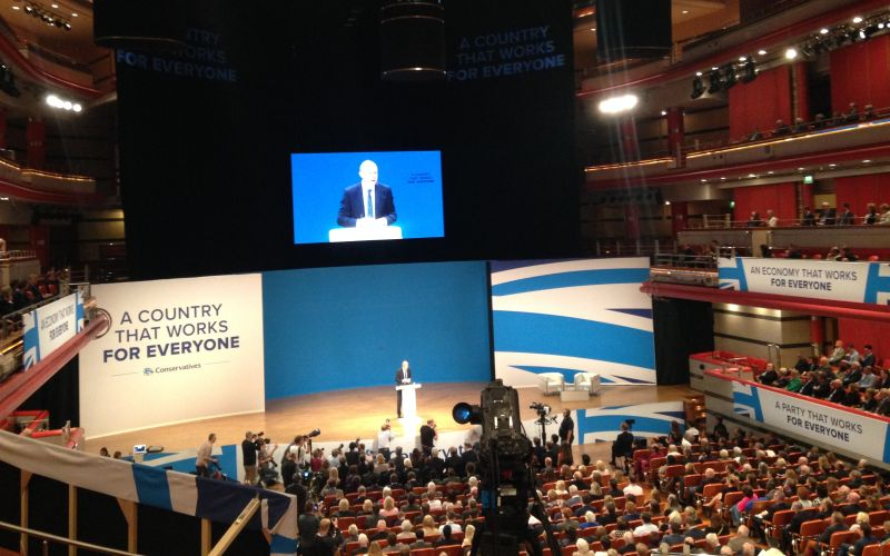 Conference audience watch Damian Green on stage