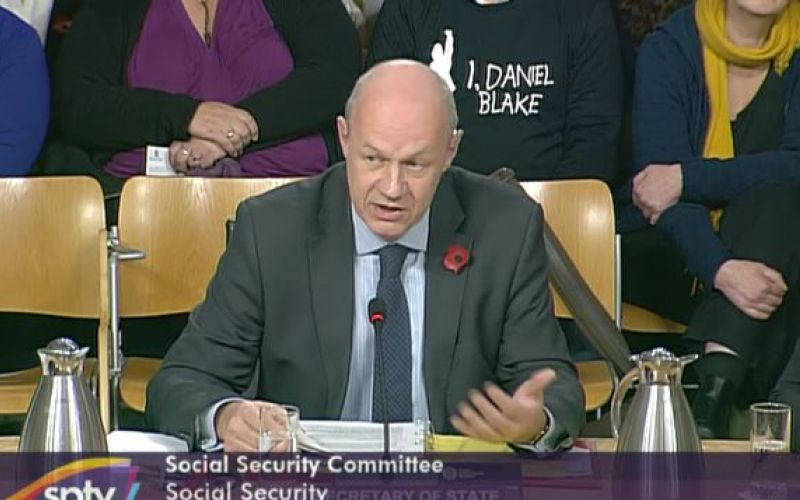 Damian Green giving evidence to MSPs, while someone behind him wears a tee shirt promoting the film I, Daniel Blake