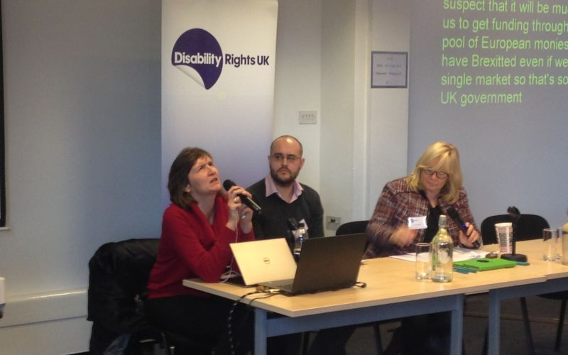 Anna Lawson speaking into a microphone watched by two other panellists