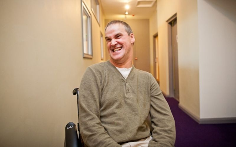 Steve Varden, smiling, in his wheelchair in a corridor