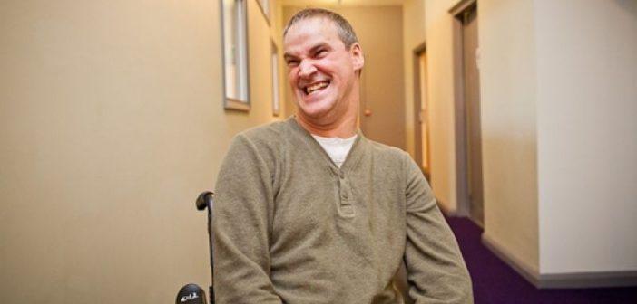 Steve Varden, smiling, in his wheelchair in a corridor
