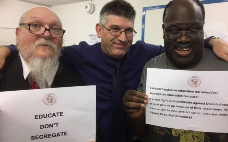 Three people looking at the camera, one holds up a sign saying educate don't segregate and another holds a sign about inclusive education