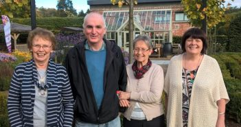 Four people stand together in a garden