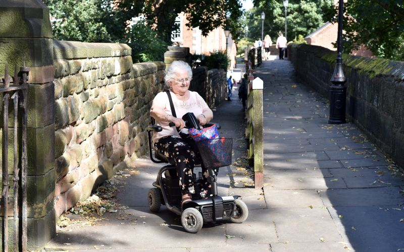 A woman guides her mobility scooter onto the historic city wall