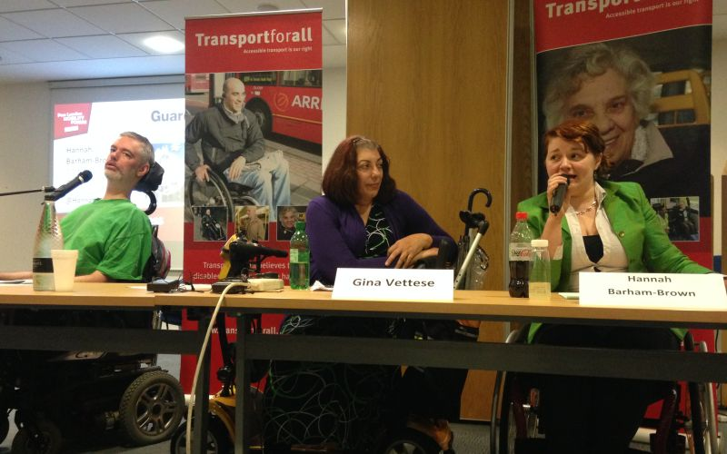 Three wheelchair-users sitting behind a table with microphones