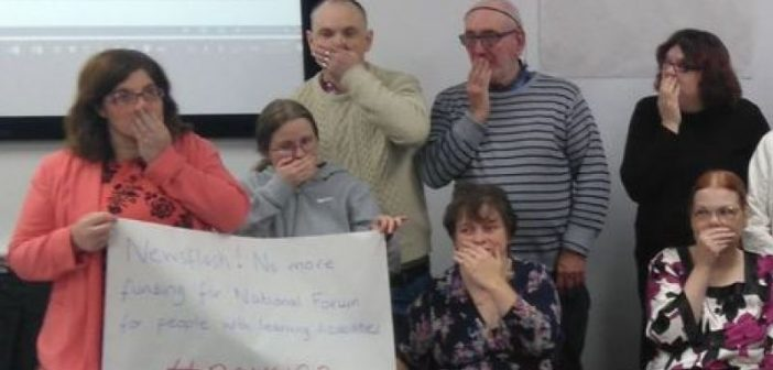 A group of people stand with their hands over their mouths