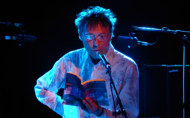 Robert Dellar on a stage, reading from a book into a microphone