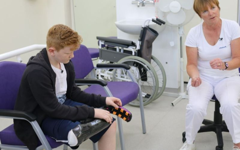 A teenager examines his new running blade, watched by a woman in a white uniform