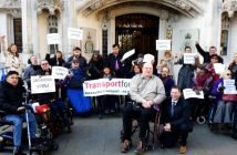 Doug Paulley in his wheelchair, surrounded by supporters outside the Supreme Court