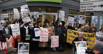 Protesters outside a jobcentre holding Lawrence Bond placards
