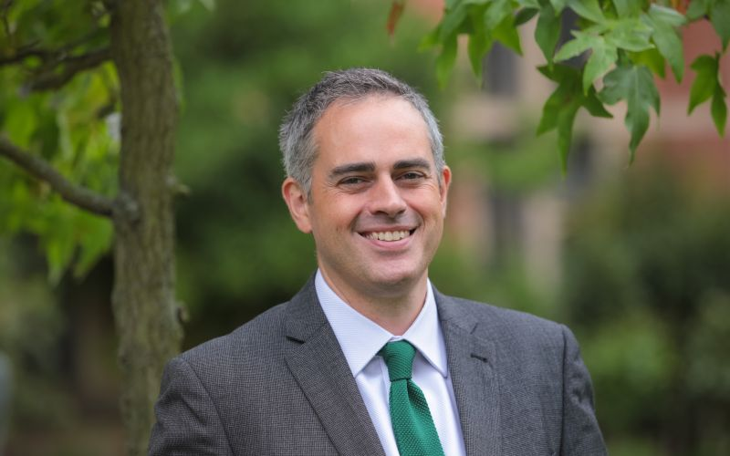 Jonathan Bartley smiling, in front of a tree