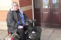Adrienne Jardine on her scooter in front of a closed door