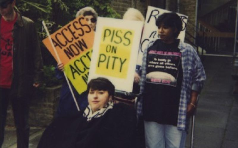 Disabled activists with Access Now and Piss On Pity placards