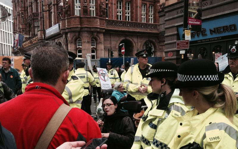 A wheelchair-user speaks into a microphone surrounded by police officers