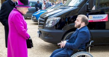 The Queen talks to a bearded man in a wheelchair, with Motability vehicles behind them