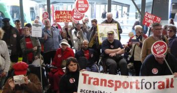Disabled protesters with placards saying Rail Access Now and Transport for All