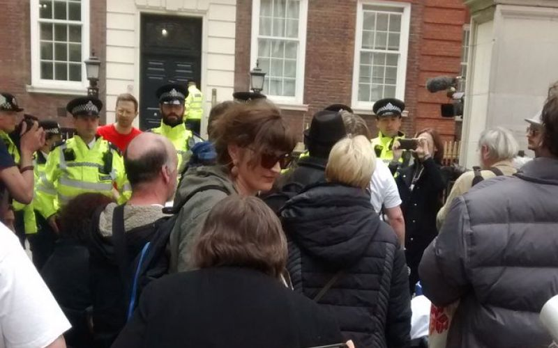 Protesters outside the Tory offices, watched by police officers