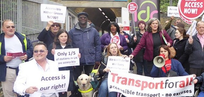 More than 30 protesters, including Heidi Alexander and wheelchair-users, with placards about access in front of a sign for Hither Green station