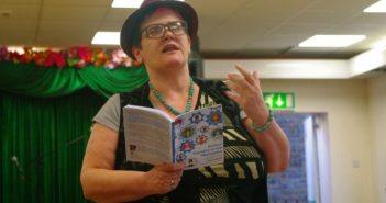 Janine Booth reading to an audience from a book