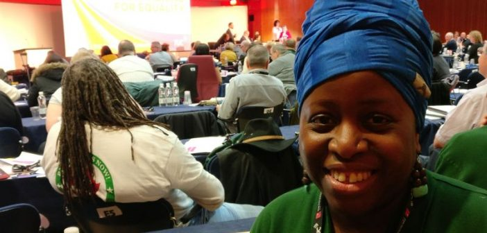 Jennifer Aggrey-Fynn smiling, in front of delegates at the conference
