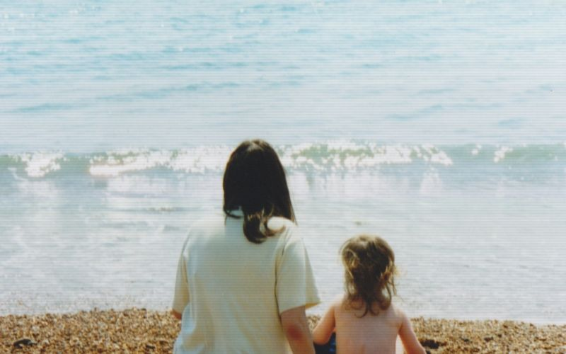A woman and a two-year-old child sit watching the sea with their backs to the camera