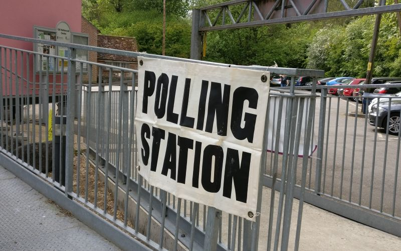 Polling station sign on a fence