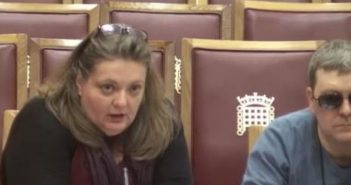 Awoman speaks into a microphone, flanked by a man, both sitting on seats with parliament's logo