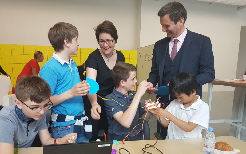 Lord Holmes and a woman talking to four children who are working with gadgets at a table