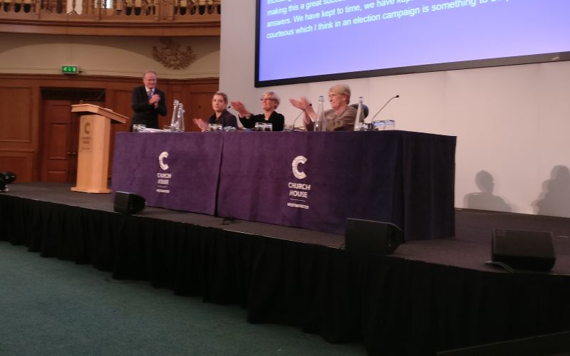 The three politicians on stage, watched by a man behind a lectern