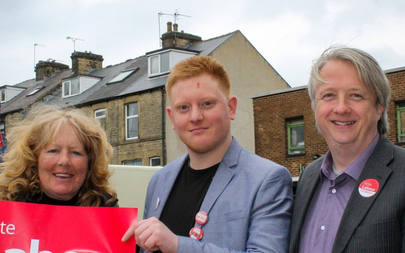 Jared O'Mara, flanked by a woman and a man, in front of a row of houses