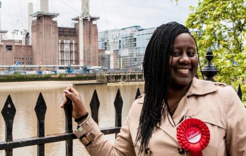 Marsha de Cordova, smiling, in front of a river, wearing a Labour rosette and holding a railing