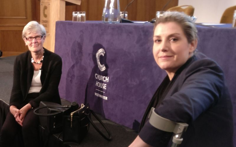 Penny Mordaunt sitting on the edge of a stage, with Labour's Kate Green sitting nearby